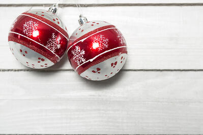 Christmas bauble decoration hanging on a light coloured wooden wall