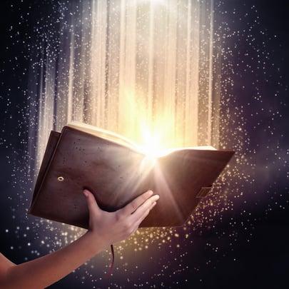 Human hand holding magic book with magic lights